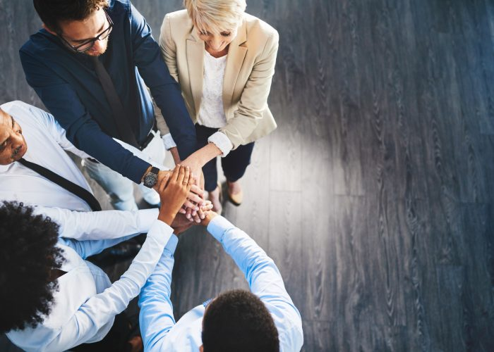Shot of a group of businesspeople joining their hands together in unity in an office